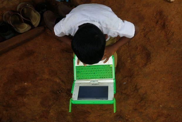 """A school boy uses a laptop provided under the """"One Laptop Per Child' project by a non-governmental organisation (NGO), in a state-run primary school in Khairat"""