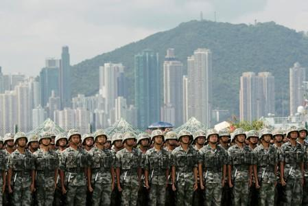 The People's Liberation Army (PLA) soldiers take part in a performance during an open day of Stonecutters Island naval base, in Hong Kong
