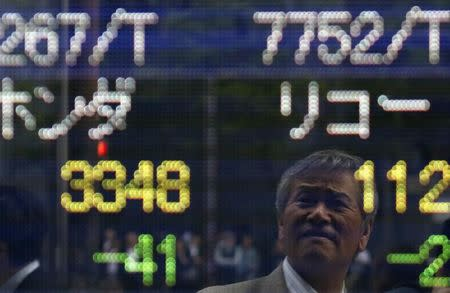 A man is reflected on an electronic stock quotation board outside a brokerage in Tokyo