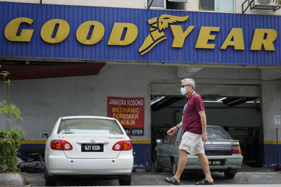 A man wearing a face mask walks in front of a Goodyear shop in Bukit Jalil, outskirts of Kuala Lumpur, Malaysia, Friday, June 11, 2021. A Malaysian court on Thursday ruled in favor of 65 migrant workers who sued U.S. tiremaker Goodyear for underpaying them, their lawyer said, calling it a victory for foreign employees. (AP Photo/Vincent Thian)