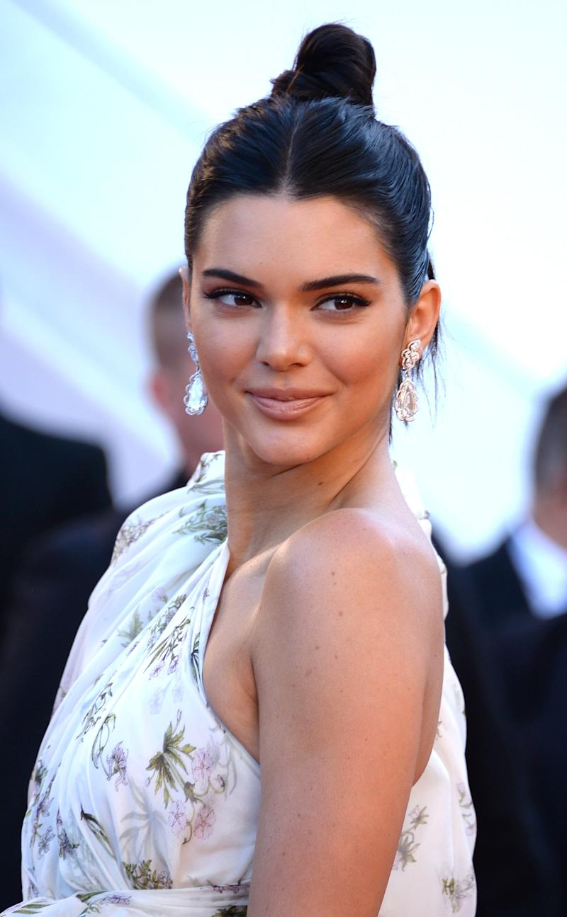 Kendall Jenner's short hair is pulled up in a sleek, modern top knot with a creamy, nude lip as she arrives at the 70th annual Cannes Film Festival.