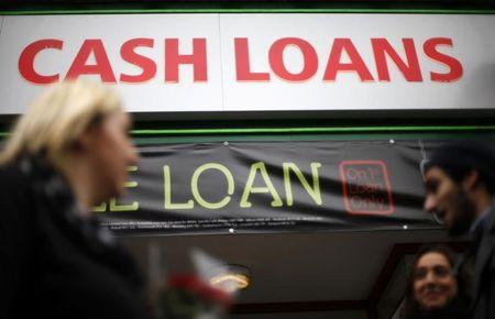 FILE PHOTO: Pedestrians pass by a lending shop in northeast London October 3, 2013.  REUTERS/Suzanne Plunkett