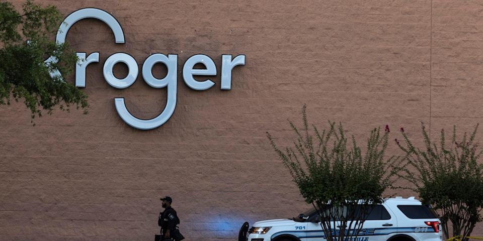A police officer walks in front of the Kroger store.