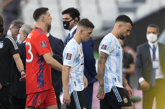 From right, Argentina's players Nicolas Otamendi, Giovani Lo Celso and goalkeeper Emiliano Martinez, walk off the field after the qualifying soccer match for the FIFA World Cup Qatar 2022 against Brazil was interrupted by health officials in Sao Paulo, Brazil, Sunday, Sept.5, 2021. (AP Photo/Andre Penner)