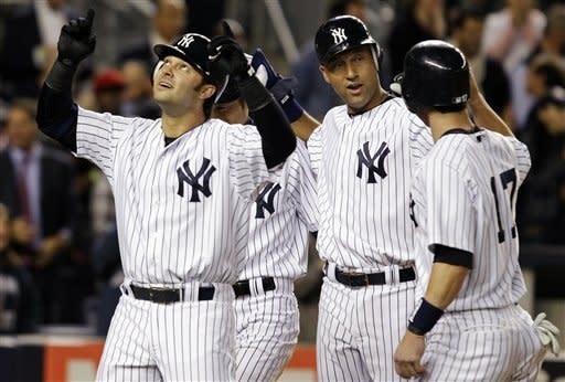 New York Yankees' Nick Swisher points skyward as Ichiro Suzuki, rear left, Derek Jeter, second from right, and Jayson Nix (17) celebrate after scoring on Swisher's fourth-inning grand slam off Toronto Blue Jays relief pitcher Brad Lincoln in their baseball game at Yankee Stadium in New York, Thursday, Sept. 20, 2012. (AP Photo/Kathy Willens)