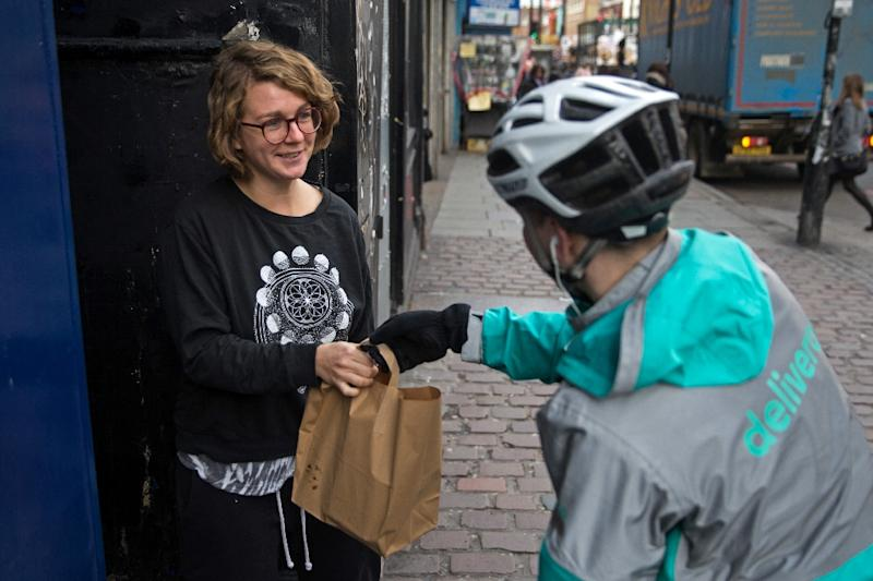 Restaurant food delivery company Deliveroo employee, Billy Shannon delivers food to a customer while working in north London November 17, 2016 (AFP Photo/Daniel Leal-Olivas)