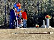 FILE - In this Feb. 23, 2021, file photo, Wanda Cooper-Jones kneels before the grave of her son, Ahmaud Arbery, at the New Springfield Baptist Church in Waynesboro, Ga., to mark the one year anniversary of Ahmaud Arbery's death in Brunswick, Ga. The Justice Department announced federal hate crime charges Wednesday, April 28, 2021, in the death of Arbery, who was killed while out for a run.(AP Photo/Lewis M. Levine, file)