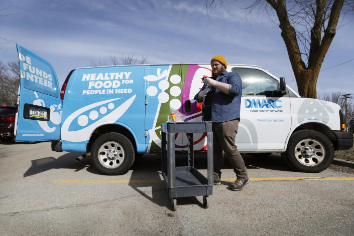 In this Tuesday, March 17, 2020, photo Des Moines Area Religious Council food pantry worker Patrick Minor prepares to pass out food at a senior center in Des Moines, Iowa. With the new coronavirus leaving many people at least temporarily out of work, food banks and pantries across the U.S. are scrambling to meet an expected surge in demand, even as older volunteers have been told to stay home and calls for social distancing have complicated efforts to package and distribute food. (AP Photo/Charlie Neibergall)