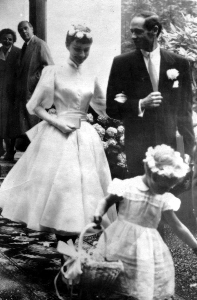 <p>For her Swiss wedding to fellow actor, and first husband, Mel Ferrer, 24-year-old Audrey Hepburn chose a tea-length flared dress with a satin sash, ballgown sleeves, and a high neck paired with elbow-length gloves. Pierre Balmain designed the look. <em>[Photo: PA]</em> </p>