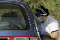 A person is tested for COVID-19 at a drive-through testing centre in a car park at Chessington World of Adventures, in Chessington, Greater London, Saturday, Sept. 19, 2020. England is preparing for more restrictions on gatherings and other activities in several areas of the country. There is growing speculation Britain may be sliding toward a lockdown in the coming weeks, partly because the testing regime is struggling to cope with higher demand. (AP Photo/Matt Dunham)