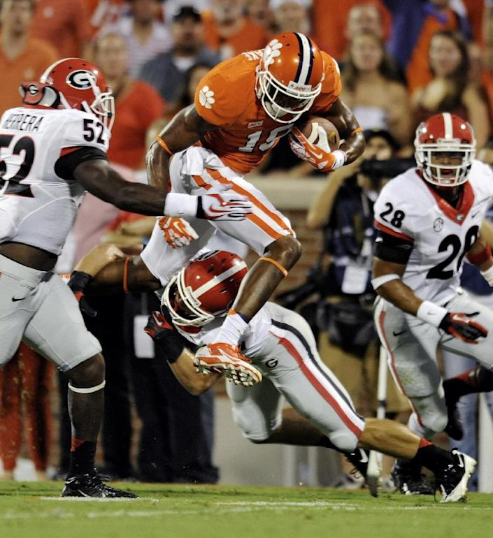 Clemson's Charone Peake leaps through the tackle of Georgia's Connor Norman, bottom, while being pursued by Amarlo Herrera during the first half of an NCAA college football game at Memorial Stadium, Saturday, Aug. 31, 2013, in Clemson, S.C. (AP Photo/Richard Shiro)