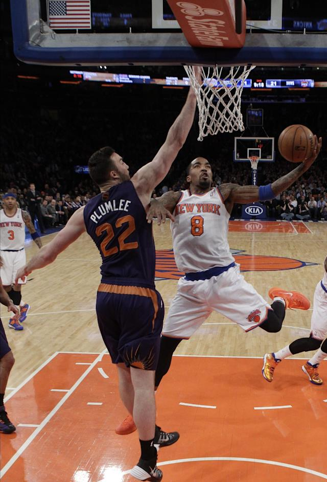 New York Knicks' J.R. Smith (8) drives past Phoenix Suns' Miles Plumlee (22) during the first half of an NBA basketball game, Monday, Jan. 13, 2014, in New York. (AP Photo/Frank Franklin II)
