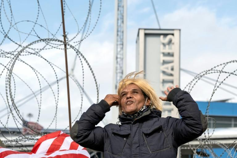 An activist impersonating Donald Trump celebrates Joe Biden's election victory on the US-Mexican border