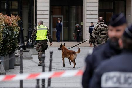 French gendarmes with a detection dog and police stand in front of the French financial prosecutor's offices following a bomb alert in central Paris