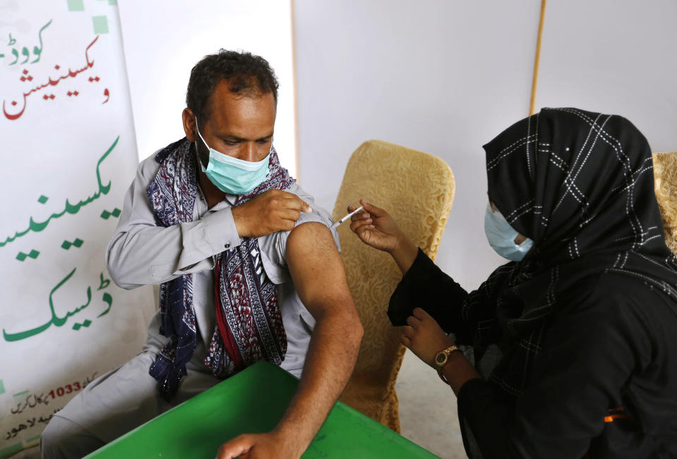 An expatriate worker receives the Moderna COVID-19 vaccine from a health worker at a vaccination center, in Lahore, Pakistan, Tuesday, July 6, 2021. Normalcy returned at COVID-19 vaccination centers across Pakistan days after Washington delivered 2.5 million doses of the Moderna vaccine to Islamabad. That enabled Pakistan's government to overcome shortages of specific vaccines which were needed to inoculate expatriate workers wishing to travel abroad. (AP Photo/K.M. Chaudary)