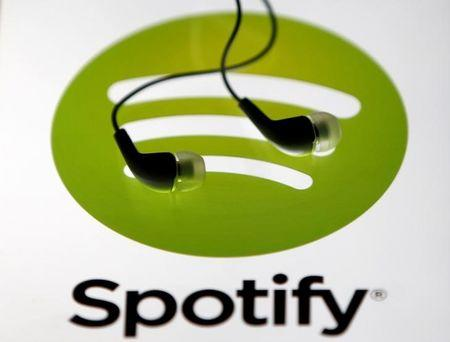 Earphones are seen on a tablet screen with a Spotify logo on it, in Zenica