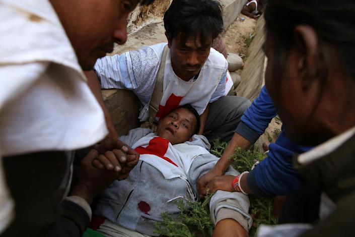 An injured Myanmar Red Cross volunteer lies on the ground after an aid convoy was attacked on February 17, 2015 (AFP Photo/-)