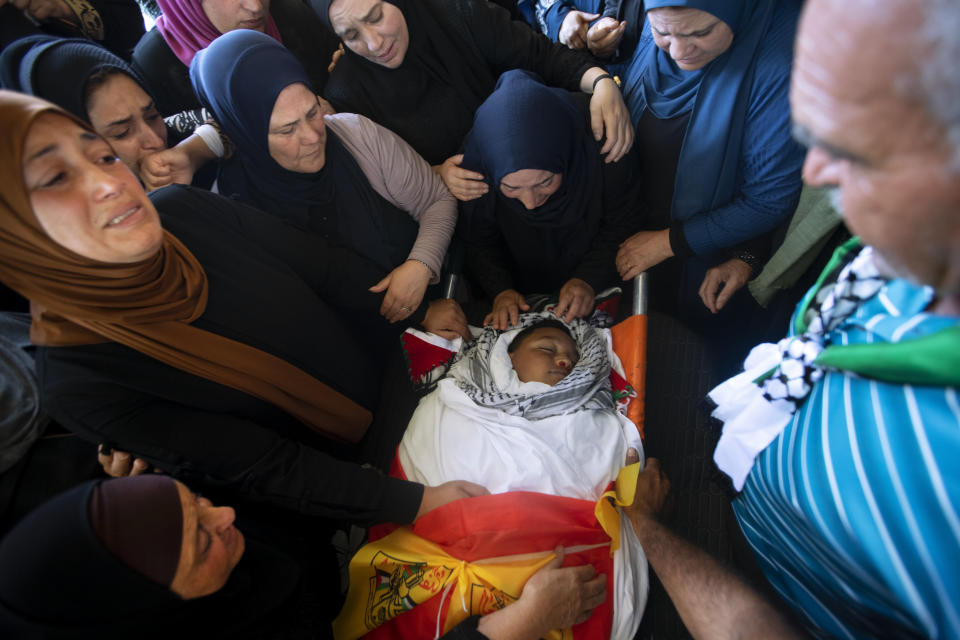 Palestinians mourn around the body of Mohammed al-Alami, 12, during his funeral in the village of Beit Ummar, near the West Bank city of Hebron, Thursday, July 29, 2021. Villagers say the boy was fatally shot by Israeli troops while traveling with his father in a car. The Israeli military has launched an investigation into the shooting. (AP Photo/Majdi Mohammed)