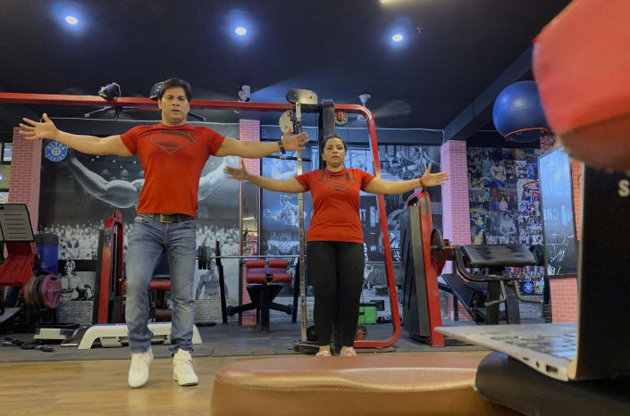 Bijender and Kanika Gautam, owners of the Ultra Bodies Fitness Studio, take online class from their closed Gyms on the outskirts of New Delhi, India, Thursday, June 10, 2021. Gyms were among the last types of venues allowed to reopen from the 2020 lockdown and they were closed again during the latest outbreaks. The Gautams had been thriving on income from their 100 gym members, making enough to rent their two-story space and pay five trainers. Now, they're relying on whatever they can scrape together from offering online fitness training, and struggling to afford rent and school fees for their two children. (AP Photo/Rishabh R. Jain)