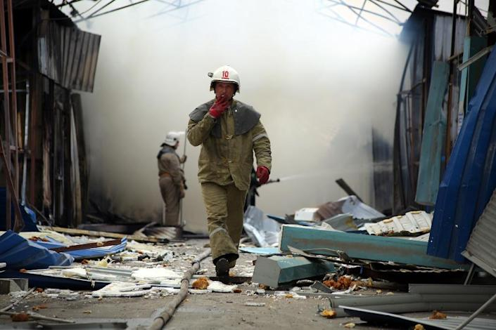A fireman works with co-workers to extinguish a fire at a market in Donetsk after shelling between Ukrainian forces and pro-Russian separatists on June 3, 2015 (AFP Photo/Aleksey Filippov)