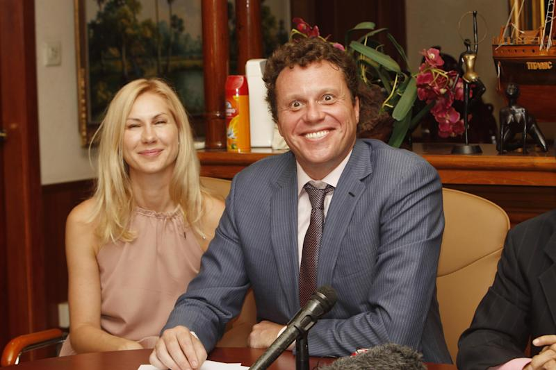 Russian businessman Sergei Polonsky, right, smiles together with his wife Olga, left, during a press conference in Phnom Penh, Cambodia, Friday, April 25, 2014. Cambodia's highest court ruled Friday that a prominent Russian property developer wanted in his homeland for allegedly embezzling millions of dollars cannot be extradited. (AP Photo/Heng Sinith)