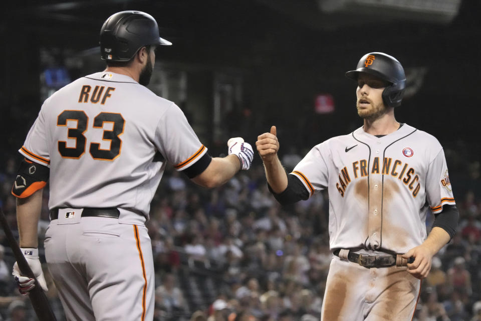 San Francisco Giants' Austin Slater celebrates with Darin Ruf (33) after scoring a run on a single hit by Buster Posey in the first inning of a baseball game against the Arizona Diamondbacks, Sunday, July 4, 2021, in Phoenix. (AP Photo/Rick Scuteri)
