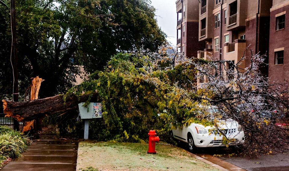 A broken tree covers a car in Oklahoma City, Okla. on Tuesday, Oct. 27, 2020, after a winter blast covered the state with ice.