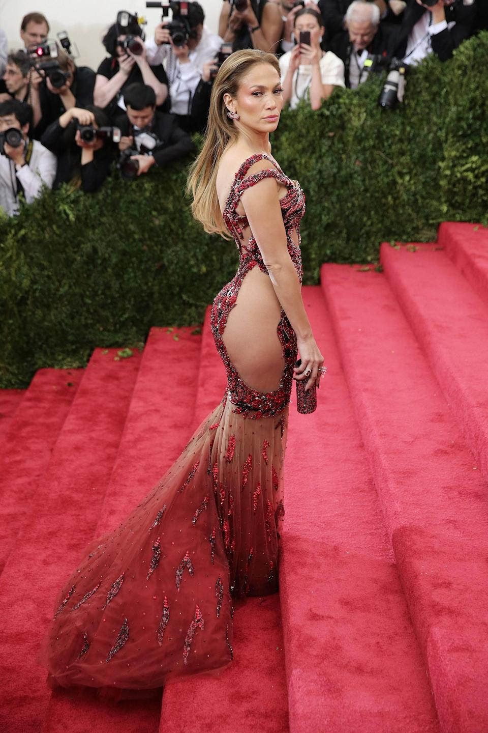<p>Going back to her Versace roots, J.Lo lit up the red carpet at Cannes in this sheer, red gown that strategically covered all of the right places. [Photo: Getty] </p>