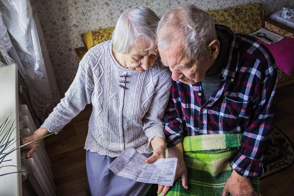 The senior woman and man holding gas bill in front of heating radiator. Payment for heating in winter.