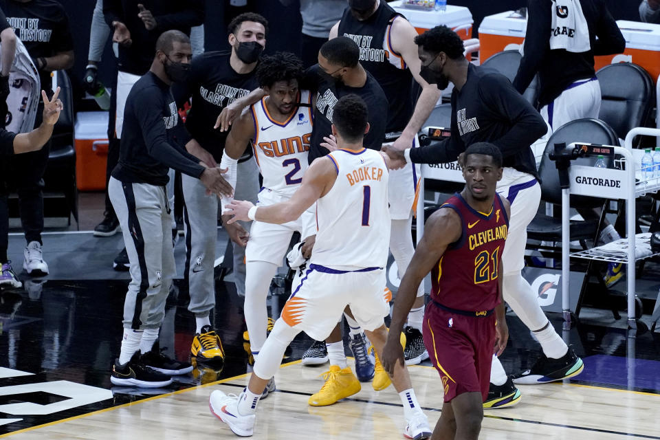 Phoenix Suns guard Langston Galloway (2) celebrates with teammates and guard Devin Booker (1) after making a shot during the first half of an NBA basketball game, Monday, Feb. 8, 2021, in Phoenix. (AP Photo/Matt York)