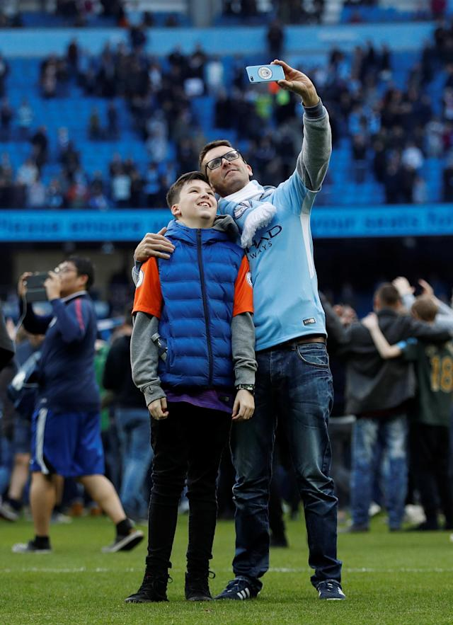 "Soccer Football - Premier League - Manchester City v Swansea City - Etihad Stadium, Manchester, Britain - April 22, 2018 Manchester City fans take selfies as they invade the pitch after the game Action Images via Reuters/Lee Smith EDITORIAL USE ONLY. No use with unauthorized audio, video, data, fixture lists, club/league logos or ""live"" services. Online in-match use limited to 75 images, no video emulation. No use in betting, games or single club/league/player publications. Please contact your account representative for further details."