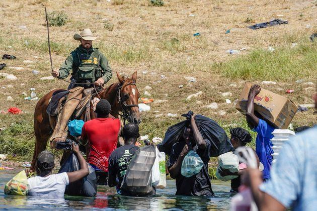 A US Border Patrol agent on horseback uses the reins as he tries to stop Haitian migrants (Photo: PAUL RATJE via Getty Images)