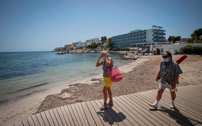 People wearing face masks arrive at Talamanca beach in Ibiza - JAIME REINA /AFP