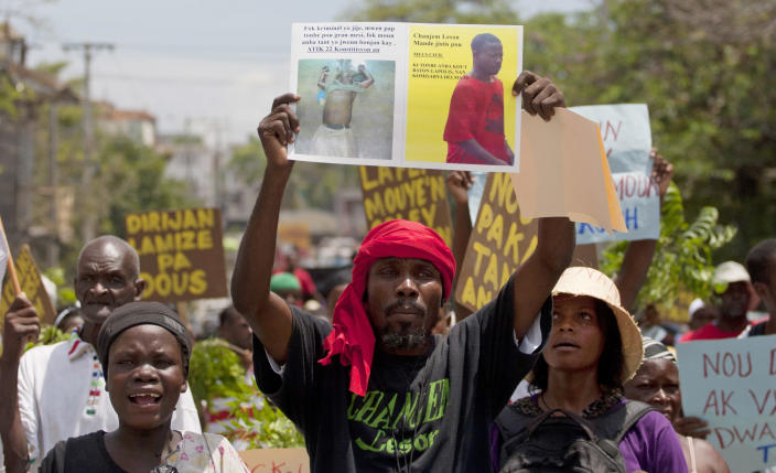 In this April 30, 2013 photo, camp leader Elie Joseph Jean-Louis holds up a photograph of the body of Merius Civil after he was allegedly beaten by police during a protest in the Delmas district of Port-au-Prince, Haiti. Civil was arrested by police early April 15, who according to his sister was taking out the trash, when police stormed the camp as residents were protesting a raid by motorcyclist who set fire to their homes. The band of motorcyclists came to Camp Acra hours after attorney Reynold Georges arrived with a judge and a police officer and told the some 30,000 people who had lost their homes in the 2010 earthquake that they were squatting on his land and had to leave, witnesses said. If they didn't vacate, he said he'd have the place burned down and leveled by bulldozers. (AP Photo/Dieu Nalio Chery)