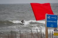 A surfer enjoys the surging surf ahead of Tropical Storm Isaias in the Rockaway area of Queens in New York