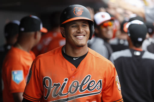 FILE - In this March 2, 2018, file photo, Baltimore Orioles' Manny Machado celebrates in the dugout after hitting a 3-run home run off Pittsburgh Pirates relief pitcher Damien Magnifico in the fourth inning of a spring training baseball game in Sarasota, Fla. In what could be his final season with the Orioles, Machado has made a seamless move from third base to shortstop. (AP Photo/John Minchillo, File)