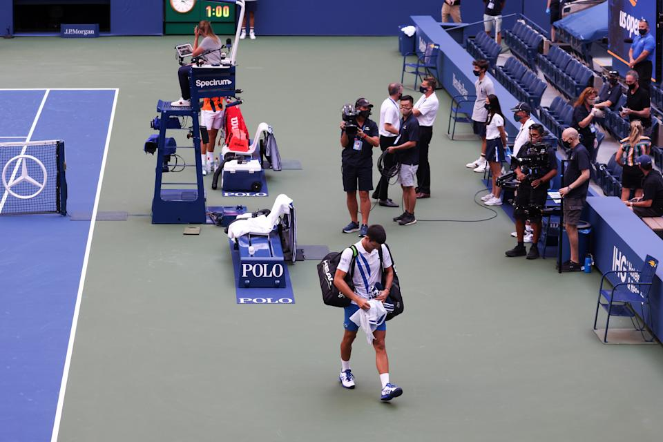 Novak Djokovic walks off the court after being defaulted due to inadvertently striking a lineswoman with a ball hit in frustration at the 2020 US Open.