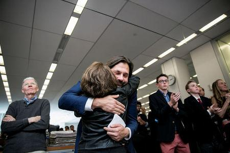 Photojournalist Daniel Berehulak, facing camera, embraces Michelle McNally, the assistant editor and director of photography of The New York Times, during announcement of the 2017 Pulitzer Prizes in The Times newsroom in New York, U.S., April 10, 2017. Berehulak won for photographs that provided a haunting portrait of a violent anti-drug campaign in the Philippines.   Sam Hodgson/Courtesy The New York Times/Handout via REUTERS