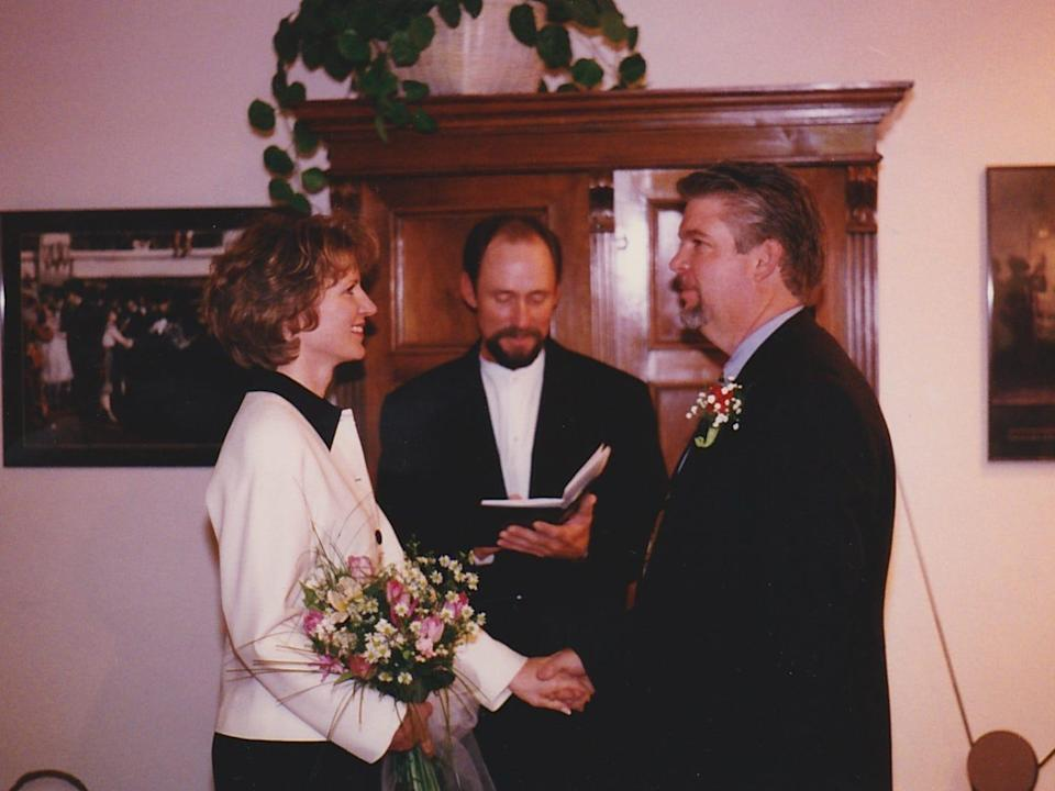 a bride and groom getting married in their living room with a minister