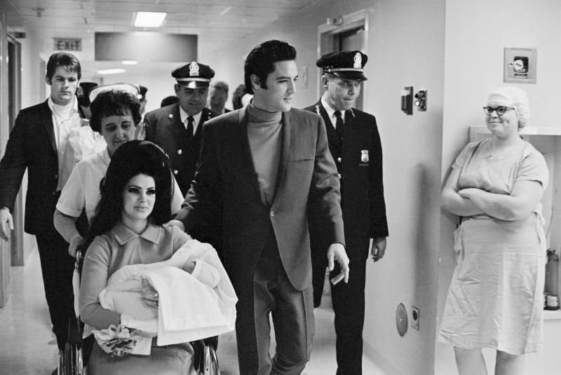 (Original Caption) 2/7/1968-Memphis, TN: Evis Presley with his wife and daughter as they leave Baptist Hospital.