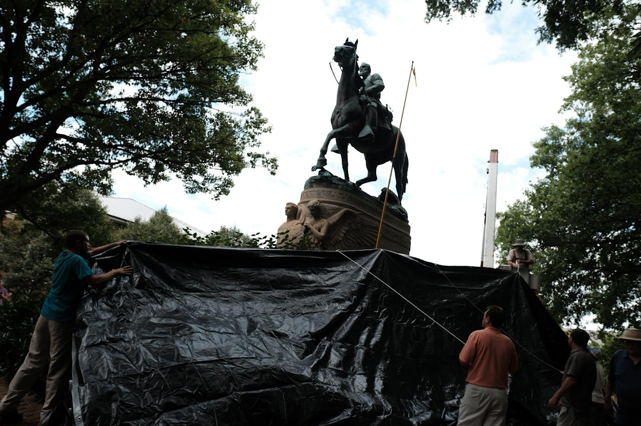 <p>Workers from the City of Charlottesville Parks Department cover the statue of Confederate General Stonewall Jackson in a black tarp in Charlottesville, Va., Aug. 23, 2017. (Photo: Justin Ide/Reuters) </p>