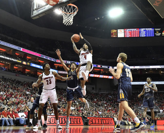 Louisville guard Khwan Fore (4) goes in for a layup past the defense of Kent State forward Akiean Frederick (3) during the second half of an NCAA college basketball game in Louisville, Ky., Saturday, Dec. 15, 2018. Louisville won 83-70. (AP Photo/Timothy D. Easley)
