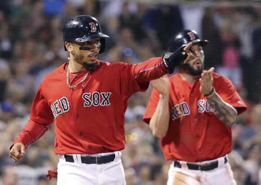 Boston Red Sox's Mookie Betts, left, gestures toward teammate J.D. Martinez after his single which drove in Betts and Blake Swihart, right, during the seventh inning of a baseball game against the Seattle Mariners at Fenway Park, Friday, June 22, 2018, in Boston. (AP Photo/Elise Amendola)