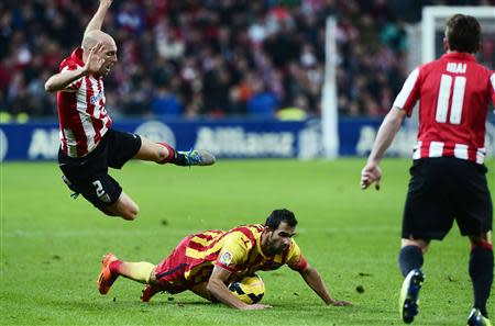 Athletic Bilbao's Gaizka Toquero falls over Barcelona's Martin Montoya during their Spanish first division soccer match at San Mames stadium in Bilbao December 1, 2013. REUTERS/Vincent West