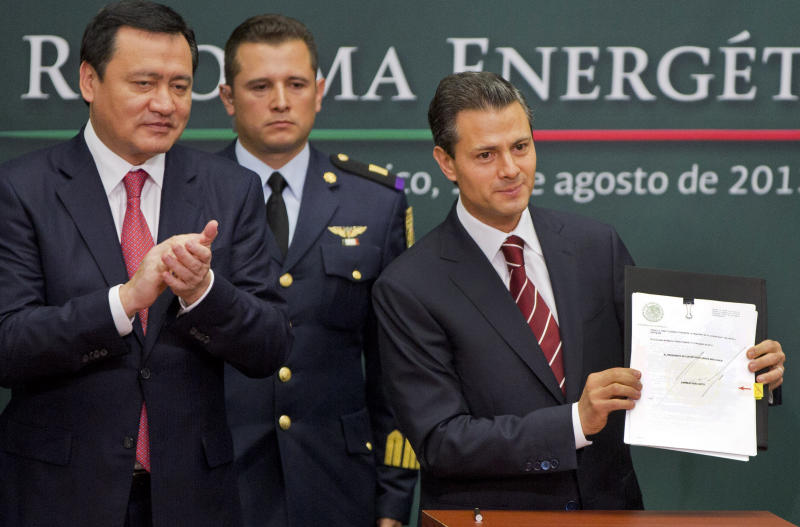 Mexico's President Enrique Pena Nieto, right, shows to the audience his proposal that would allow private firms to participate in the oil industry as his Interior Secretary Miguel Angel Osorio Chong applauds in Mexico City, Monday, Aug.12, 2013. Pena Nieto is making his most daring gamble yet, with a proposal to lift a decades-old ban on private companies in the state-run oil industry, a cornerstone of Mexico's national pride. (AP Photo/Eduardo Verdugo)