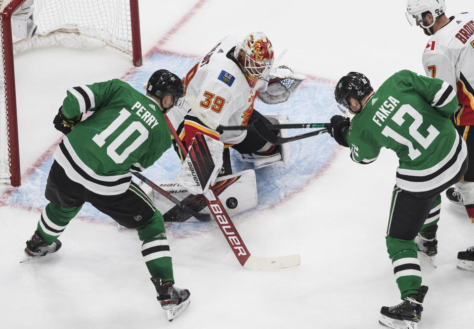 Calgary Flames goalie Cam Talbot (39) makes the save on Dallas Stars' Corey Perry (10) as Stars' Radek Faksa (12) tries to get the rebound during the second period of a first round NHL Stanley Cup playoff hockey series in Edmonton, Alberta, on Thursday, Aug. 13, 2020. (Jason Franson/The Canadian Press via AP)