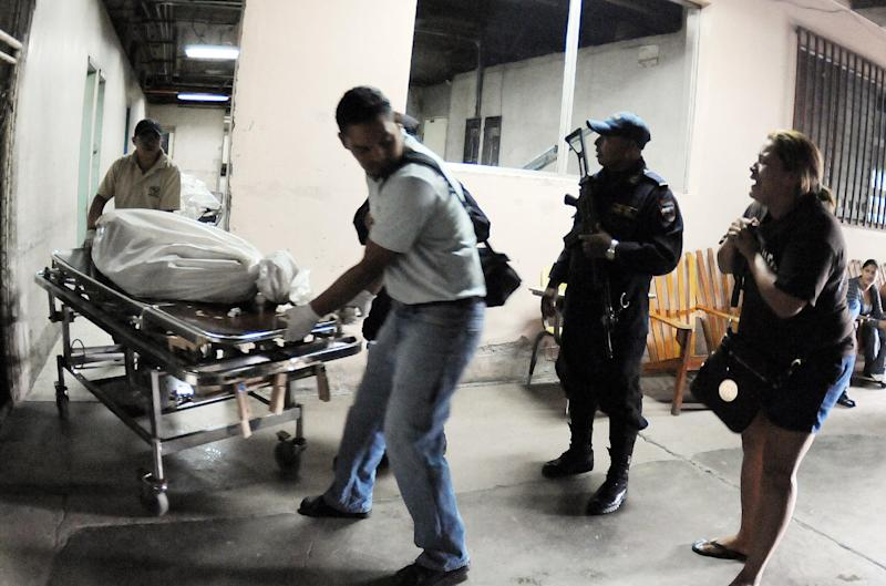 Forensic workers transport the body of a prisoner from inside the Hospital Escuela to a waiting vehicle, in Tegucigalpa, Honduras, Saturday, Aug. 3, 2013.A riot at the country's main prison left at least three gang members dead and several guards injured. Police said members of the 18 gang clashed with common criminals in Honduras' National Penitentiary, located 10 miles (15 kilometers) north of the capital. Ambulances had taken three injured gang members from the prison to Hospital Escuela, where they died. (AP Photo/Fernando Antonio)