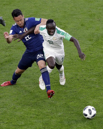 Japan's Maya Yoshida, left, and Senegal's Sadio Mane battle for the ball during the group H match between Japan and Senegal at the 2018 soccer World Cup at the Yekaterinburg Arena in Yekaterinburg , Russia, Sunday, June 24, 2018. (AP Photo/Mark Baker )