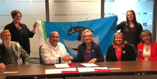 NCC president Todd Russell, second from left, signed a memorandum of understanding in September 2019. (Nunatukavut.ca - image credit)