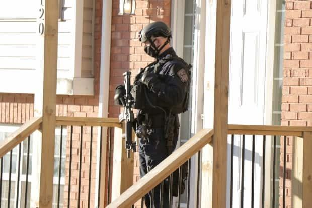 An armed Halifax Regional Police officer guarded the entrance to a home on Larry Uteck Boulevard in Bedford following a Friday morning drug raid.  (Paul Palmeter/CBC - image credit)